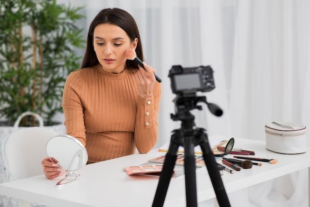 Frau, die ihr make-up auf kamera tut