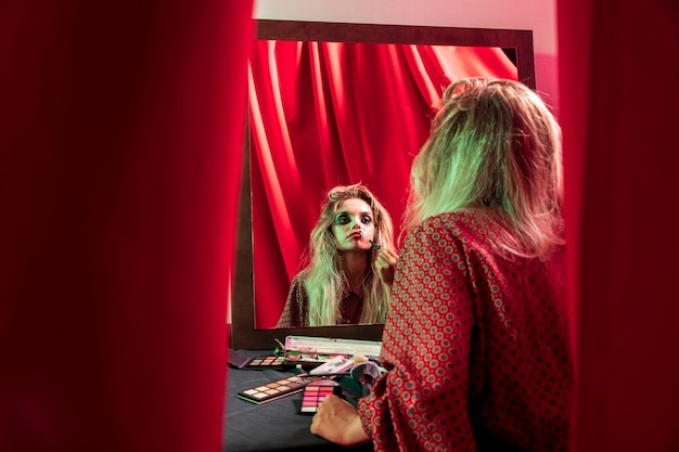 Frau, die ihr make-up im spiegel repariert