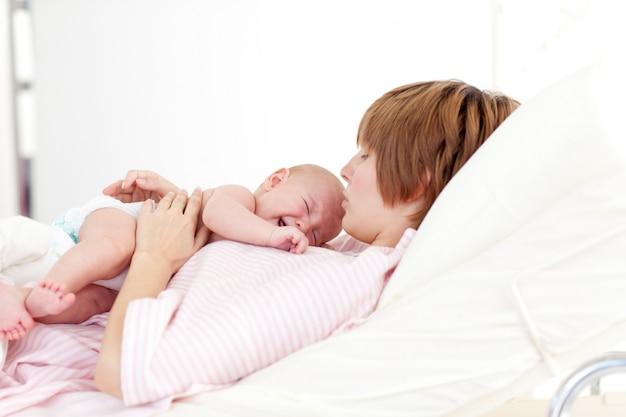 Frau, die ihr neugeborenes baby küsst