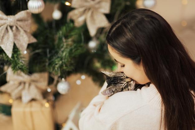 Frau, die ihr schlafendes kätzchen umarmt und küsst.