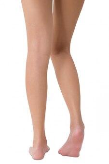 Frau, die ihr schönes langes bein lokalisiert auf weiß aufwirft