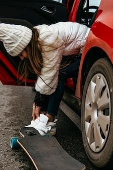 Frau, die ihr skateboard aus dem auto holt