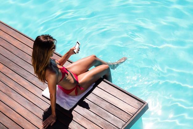 Frau, die ihr smartphone am poolrand verwendet