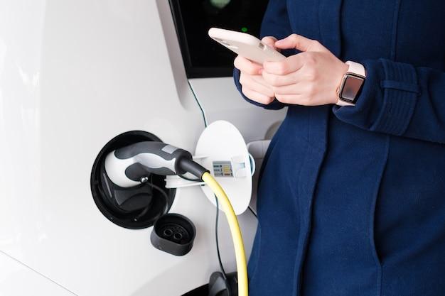 Frau, die ihr smartphone benutzt, während das elektroauto oder ev fahrzeug auf dem parkplatz auflädt