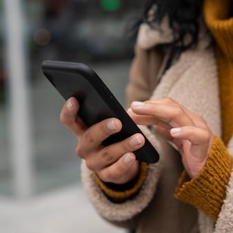 Frau, die ihr smartphone draußen benutzt