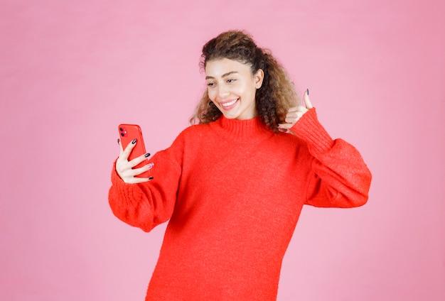 Frau, die ihr smartphone hält und ihr selfie nimmt.
