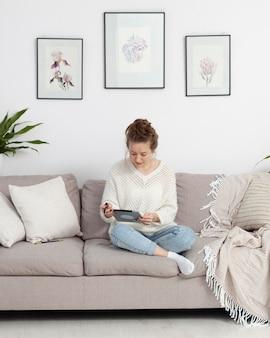 Frau, die ihr tablett benutzt, um einen blog zu schreiben