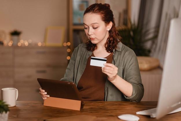 Frau, die ihr tablett zu hause mit kreditkarte verwendet