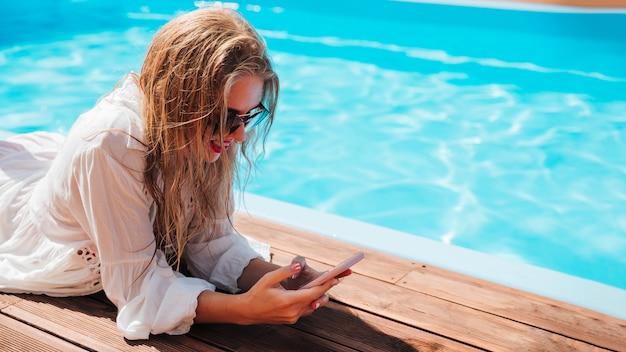 Frau, die ihr telefon am pool überprüft