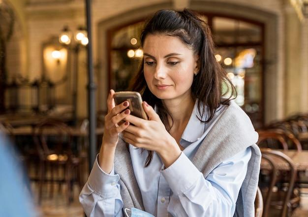 Frau, die ihr telefon im restaurant überprüft