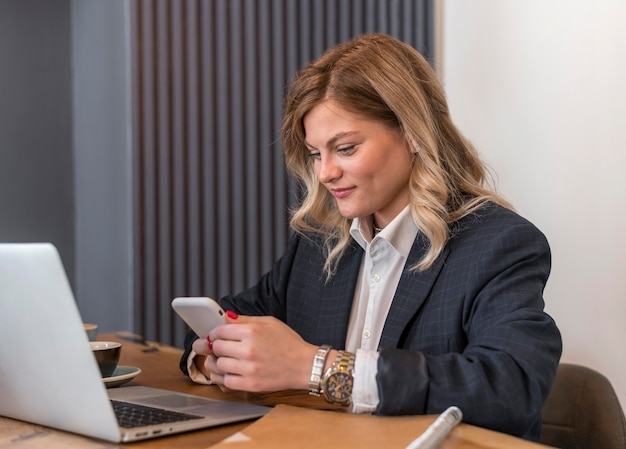 Frau, die ihr telefon in einer besprechung überprüft