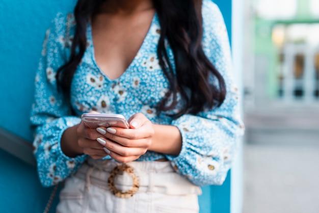 Frau, die ihr telefon mit blauem hintergrund verwendet