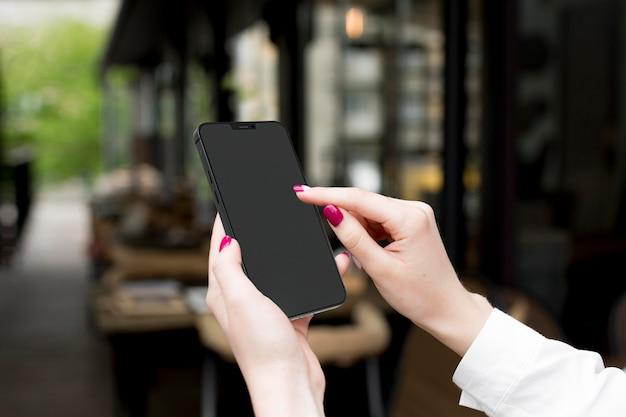 Frau, die ihr telefon mit leerem bildschirm betrachtet