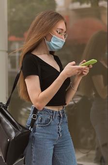 Frau, die ihr telefon überprüft, während sie eine medizinische maske trägt
