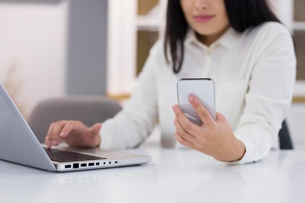 Frau, die ihr telefon und laptop für cyber-montag-ereignis überprüft