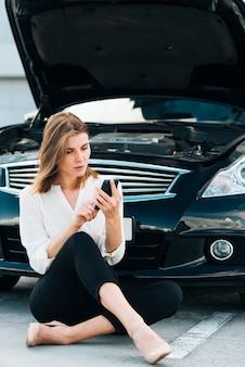 Frau, die ihr telefon und schwarzes auto überprüft