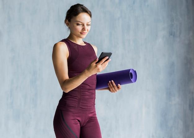Frau, die ihr telefon während ihres trainings betrachtet