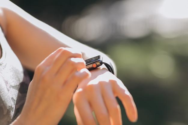 Frau, die ihr tragbares technologiegerät des smartwatch mit berührungseingabe bildschirms in den morgenlichtern verwendet