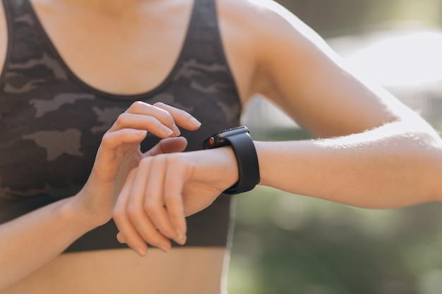 Frau, die ihr tragbares technologiegerät des smartwatch mit berührungseingabe bildschirms verwendet