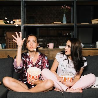 Frau, die ihr werfendes popcorn der freundin beim überwachen des filmes betrachtet
