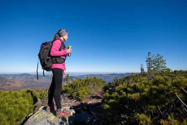 Frau, die ihr ziel steht auf spitze des berges erreicht