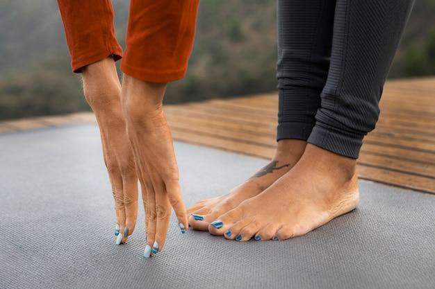 Frau, die ihre arme zu ihren zehen streckt, während yoga draußen macht