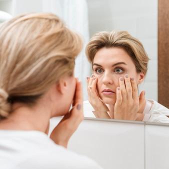 Frau, die ihre augen im spiegel prüft