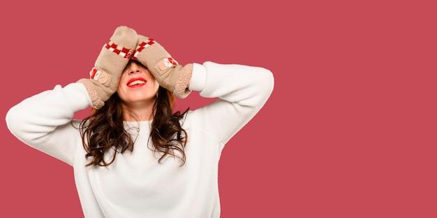 Frau, die ihre augen mit flaumigen handschuhen bedeckt