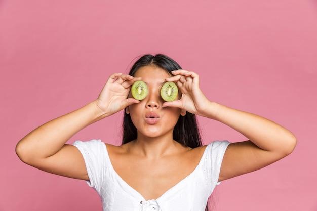 Frau, die ihre augen mit kiwi auf rosa oberfläche bedeckt