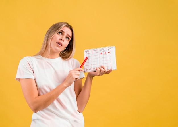 Frau, die ihre augen rollt und den menstruationskalender zeigt