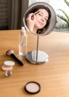 Frau, die ihre augenbrauen im spiegel tut