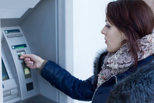 Frau, die ihre bankkarte am geldautomaten abholt und darauf wartet, dass sie aus dem schlitz ausgegeben wird, nachdem sie eine bargeldabhebung vorgenommen hat