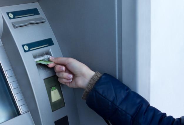 Frau, die ihre bankkarte am geldautomaten vor einer bank einführt, damit sie durch eingabe ihres pin-codes bargeld abheben kann