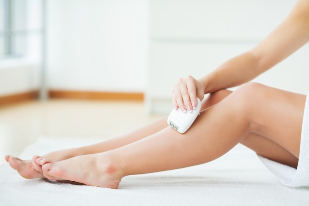 Frau, die ihre beine im badezimmer rasiert
