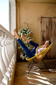 Frau, die ihre bequeme terrasse genießt. junge frau, die auf stuhl liegt und zu hause entspannt.