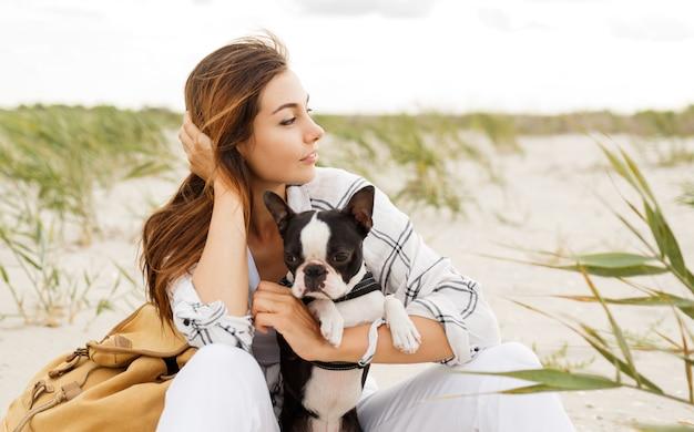 Frau, die ihre bulldogge am strand im sonnenuntergangslicht, sommerferien umarmt. stilvolles mädchen mit lustigem hund, der sich ausruht, umarmt und spaß hat, süße momente.