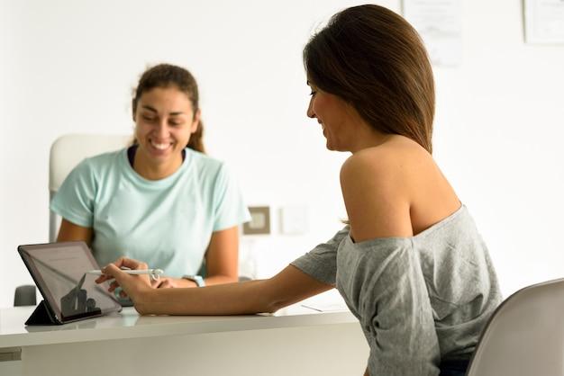 Frau, die ihre diagnose mit weiblichem physiotherapeuten annimmt und unterzeichnet.