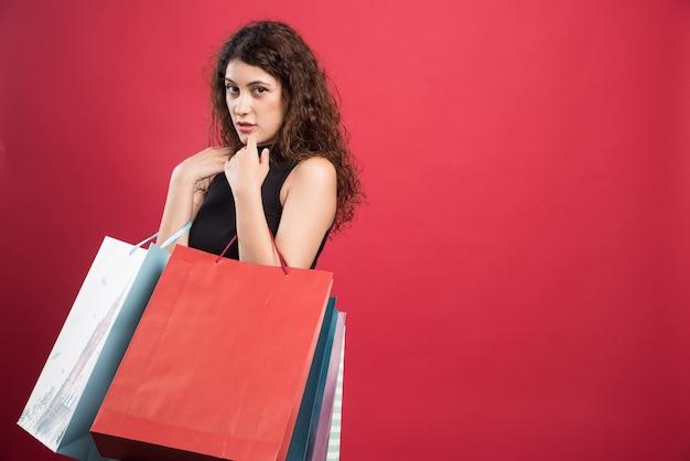 Frau, die ihre einkäufe auf rotem hintergrund zeigt. hochwertiges foto