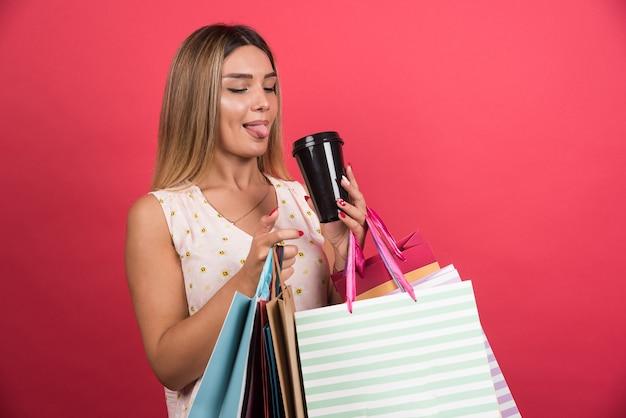 Frau, die ihre einkaufstaschen hält und tasse kaffee auf roter wand trinkt.