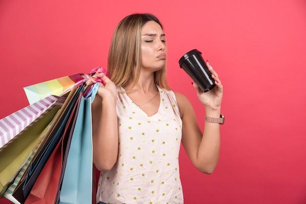 Frau, die ihre einkaufstaschen hält und tasse kaffee trinkt.