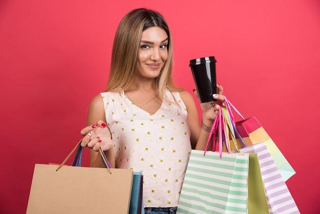 Frau, die ihre einkaufstaschen und tasse auf roter wand hält.
