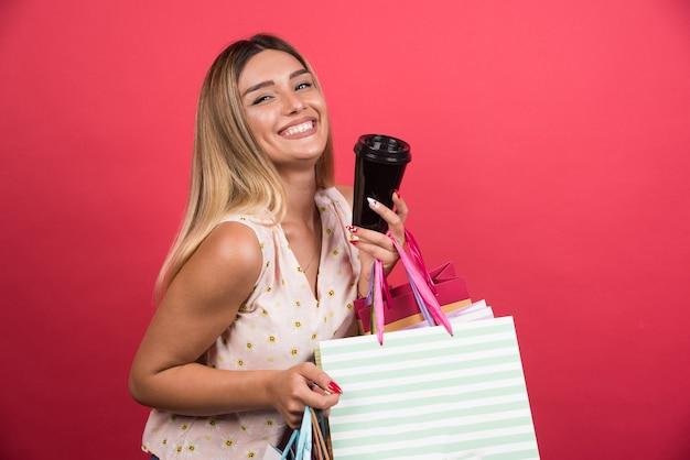 Frau, die ihre einkaufstaschen und tasse auf roter wand zeigt.