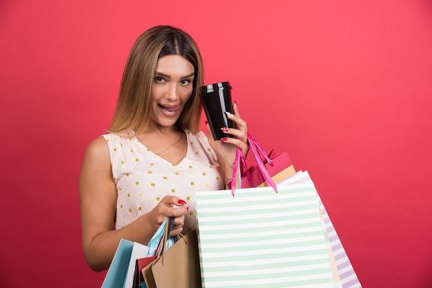 Frau, die ihre einkaufstaschen und tasse kaffee auf roter wand zeigt.