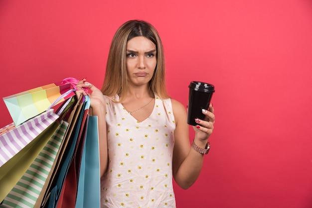 Frau, die ihre einkaufstaschen und tasse kaffee unangenehm auf roter wand hält.