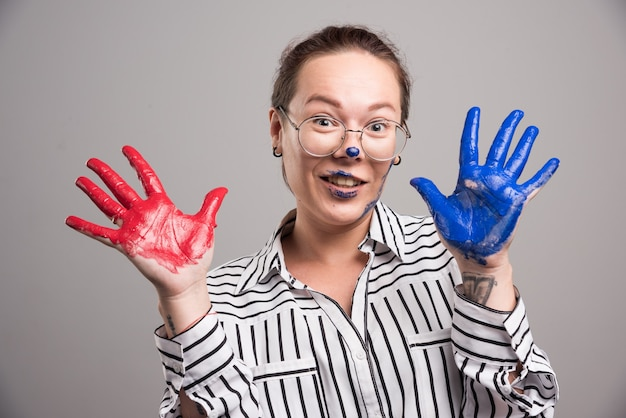 Frau, die ihre farbenhände auf grauem hintergrund zeigt