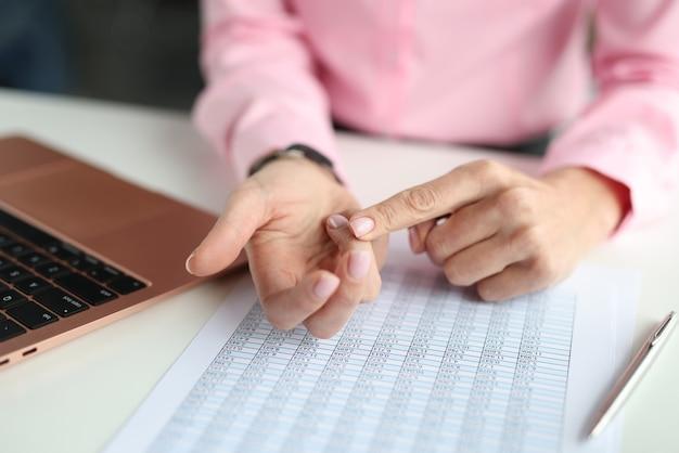 Frau, die ihre finger über tisch mit zahlen und laptop-nahaufnahme kräuselt. buchhaltung und planung