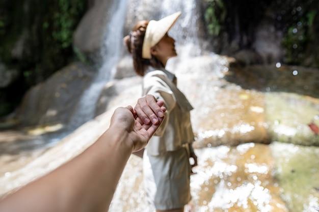 Frau, die ihre freundhandhand zum wasserfall im tropischen regenwald hält. saiyok noi wasserfall, gelegen in der provinz kanchanaburi, thailand.