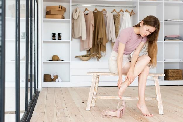 Frau, die ihre füße nach dem tragen der hohen absätze mitteilt