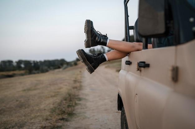 Frau, die ihre füße über auto während des reisens hängt