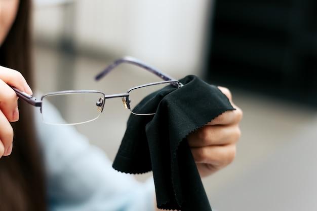 Frau, die ihre gläser mit schwarzem stoff säubert.